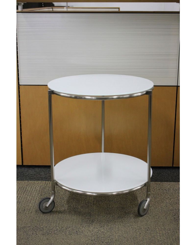 """Pre-owned two-tier round side table has frosted white surfaces. Features (3) chrome legs on casters. Dimensions: 20""""W in diameter x 24""""H."""