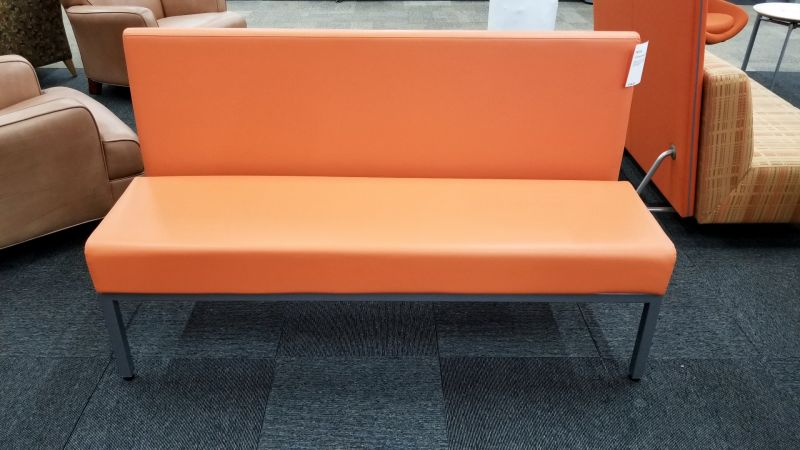 Pre-owned CHI sofa has orange leather upholstery and a chrome base with (4) post legs.