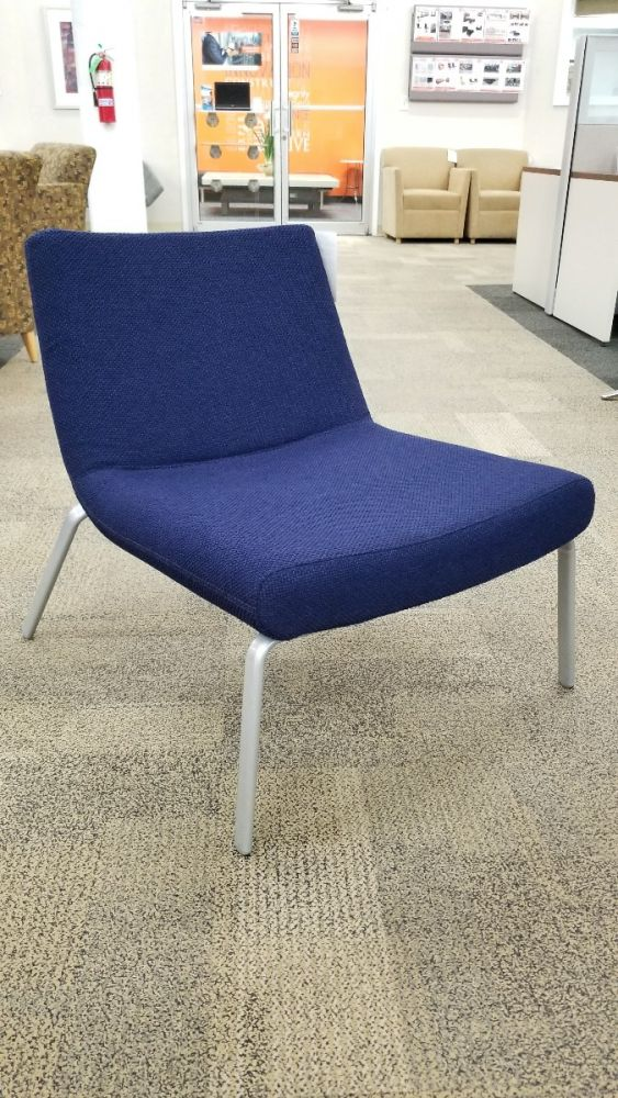 Pre-owned Keilhauer Celia lounge chair has blue upholstered body and (4) metallic silver post legs.