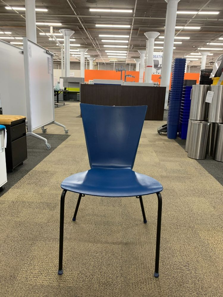 Front view of Pre-owned Lowenstein stack chair has a blue plastic body with (4) black post legs. -C GRADE-