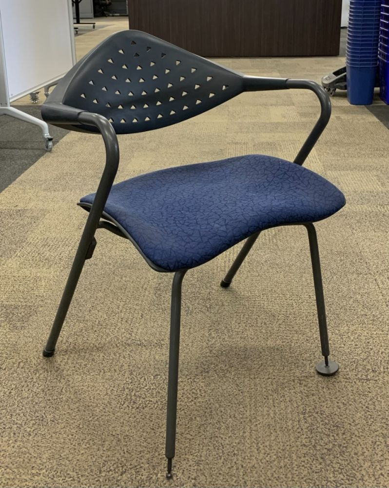Pre-owned Sitag stack chair has blue triangle patterned upholstered seat and a black perforated plastic back.