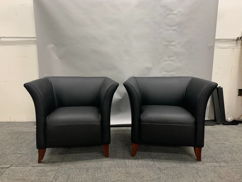 pair of OSP lounge chairs have black leatherette body with (4) cherry post legs