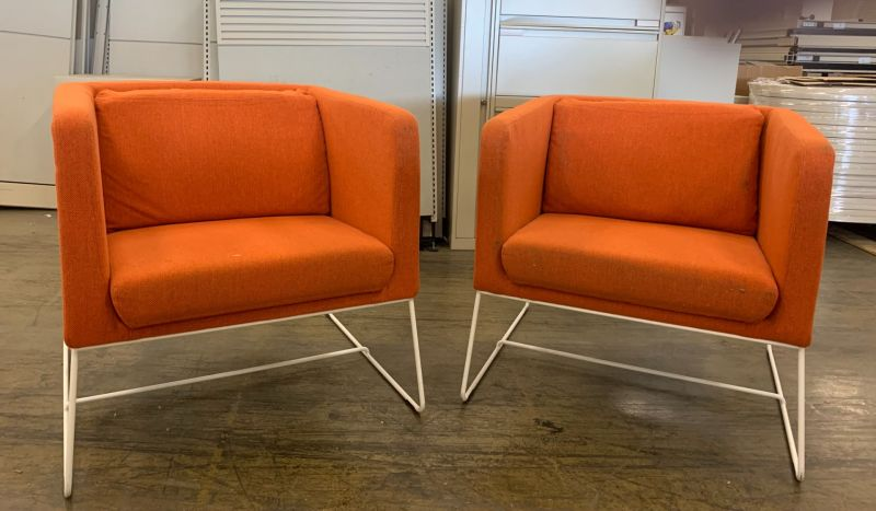The pair of lounge chairs have orange stitch upholstery and a white wire sled base.