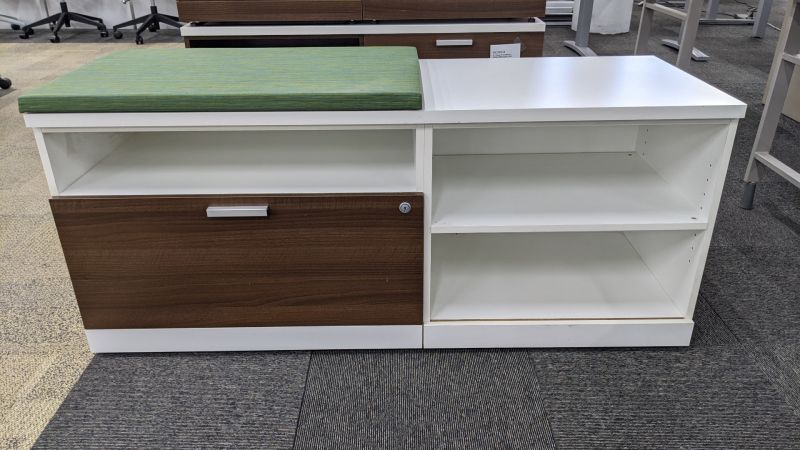 "Pre-owned Three H credenza has a white laminate finish. Left-handed. With (1) lateral file drawer with mahogany front, 2H shelving, (1) cubbie and a green line patterned cushion top. Dimensions: 20""D x 48""W x 24""H. -A GRADE-"