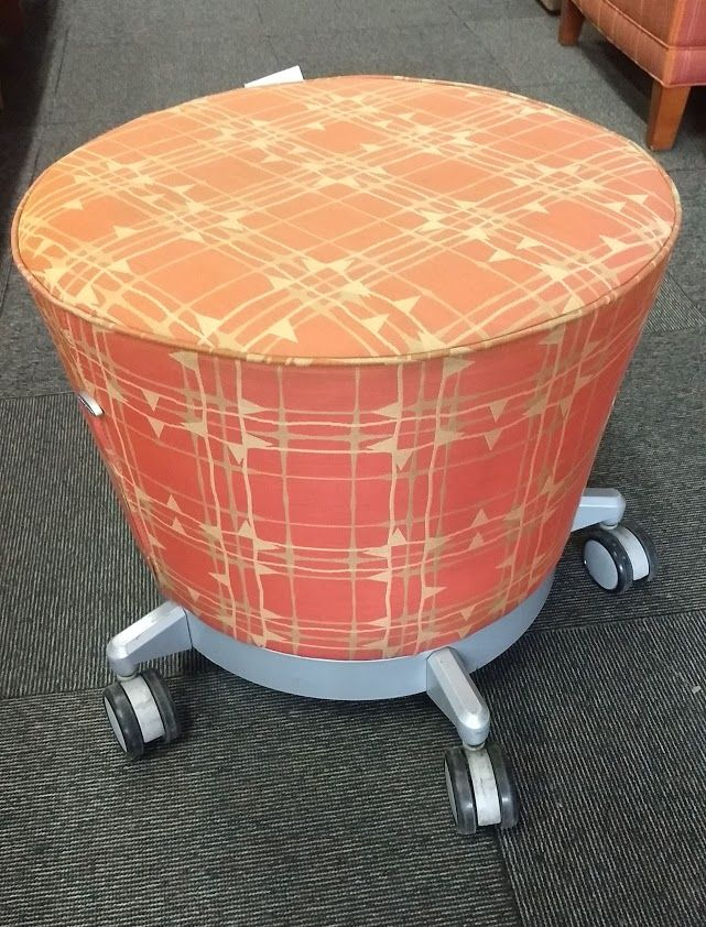 Pre-owned Haworth Hello mobile ottoman has orange square patterned fabric body. Metallic silver base with (5) casters