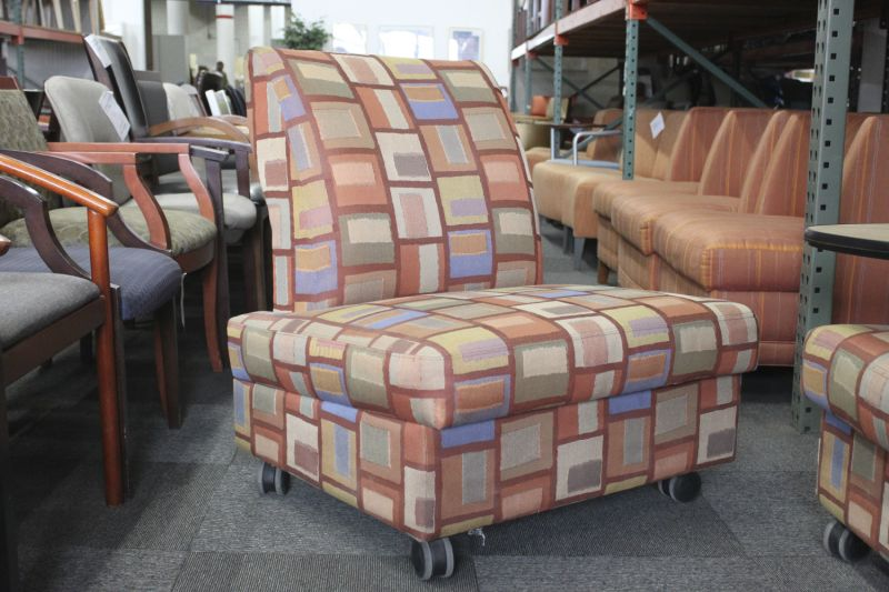 Pre-owned Metro lounge chair has orange square patterned upholstery. With right-handed maple tablet arm with black edge banding.
