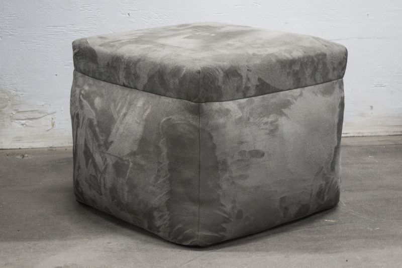 Pre-owned cube-shaped ottoman has grey fabric upholstery.