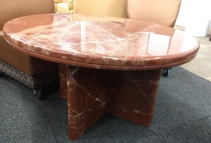"""Pre-owned round coffee table has orange marble surface and matching interlocking X-base. Dimensions: 38""""W in diameter x 21""""H."""