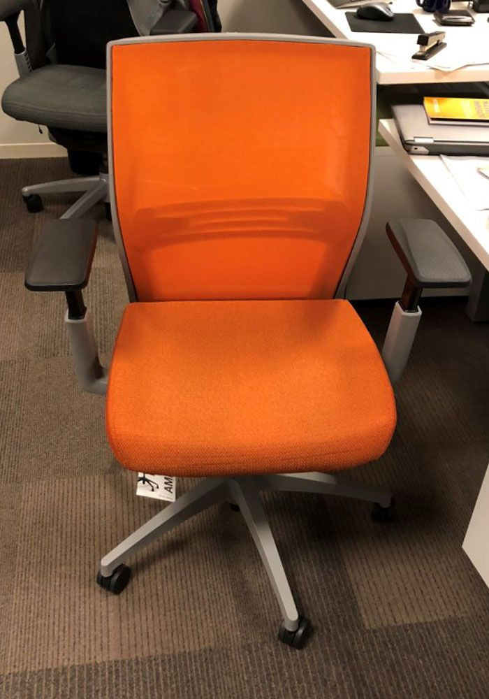 Pre-owned Sit On It Amplify task chair has orange seat and mesh back.