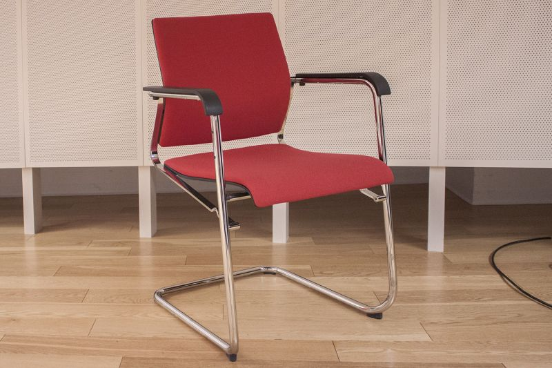 Pre-owned Wilkhahn stack chair has red fabric upholstery, a chrome sled base and black armpads.