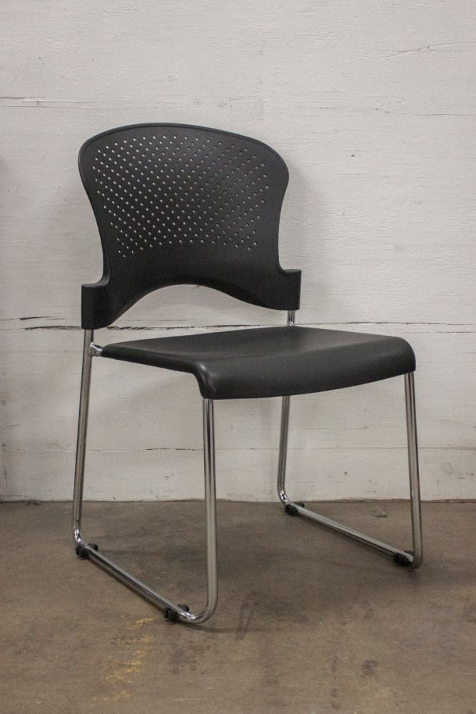 Pre-owned stack chair has black plastic seat with perforated black. With chrome sled base.